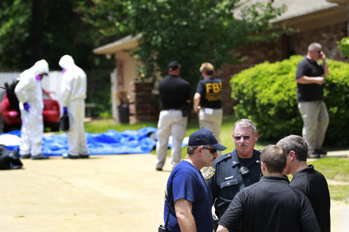 FILE - In this May 31, 2013 file photo, authorities search a residence in New Boston, Texas in connection with a federal investigation surrounding ricin-laced letters mailed to President Barack Obama and New York Mayor Michael Bloomberg. Two U.S. law enforcement officials say Shannon Richardson of New Boston, Texas, has been arrested Friday, June 7, in the investigation. (AP Photo/Texarkana Gazette, Evan Lewis, File) MANDATORY CREDIT