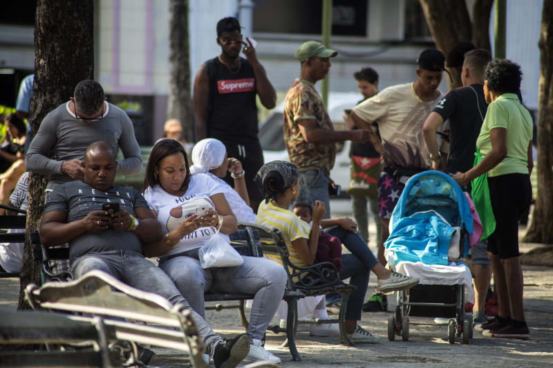 People surf the internet on their smartphones at a government-sponsored Wi-Fi spot at a park in Havana, Cuba, Thursday, Dec. 6, 2018. For the first time, Cubans are able to sign up for 3G internet service for their mobile phones, with packages ranging from 600 megabytes for about $7 to four gigabytes for about $30 month. (AP Photo/Desmond Boylan)