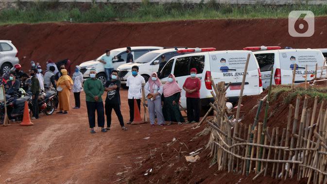 Kerabat menyaksikan proses pemakaman jenazah dengan protokol COVID-19 di TPU Pondok Ranggon, Jakarta, Sabtu (19/9/2020). Hingga Sabtu (19/9), angka positif COVID-19 di Indonesia bertambah menjadi 240.687 orang, sembuh 174.350 dan meninggal dunia 9.448. (Liputan6.com/Helmi Fithriansyah)