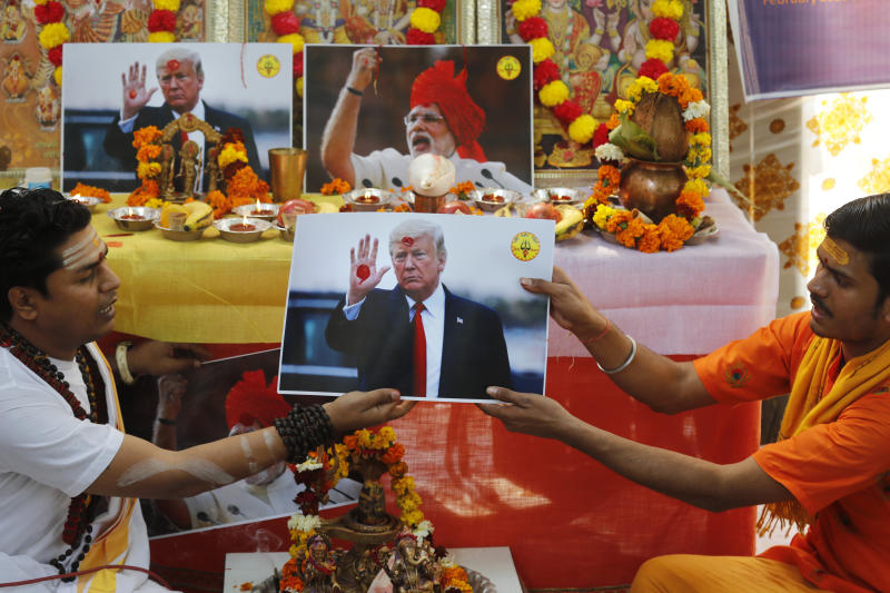 Hindu priests offer prayers holding a portrait of U.S. President Donald Trump in New Delhi, India, Monday, Feb. 24, 2020. The prayer event was held by Hindu Sena for a successful Trump visit and for world peace. (AP Photo/Manish Swarup)