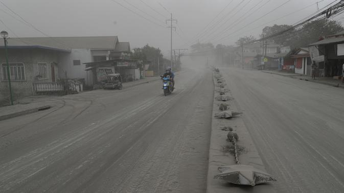 Pengendara sepeda motor melintasi jalan yang tertutup abu vulkanik dari gunung berapi Taal di Lemery, provinsi Batangas, Filipina, Senin (13/11/2020). Erupsi gunung Taal memaksa puluhan ribu orang mengungsi serta membuat sekolah-sekolah dan toko di Manila tutup. (AP/Aaron Favila)