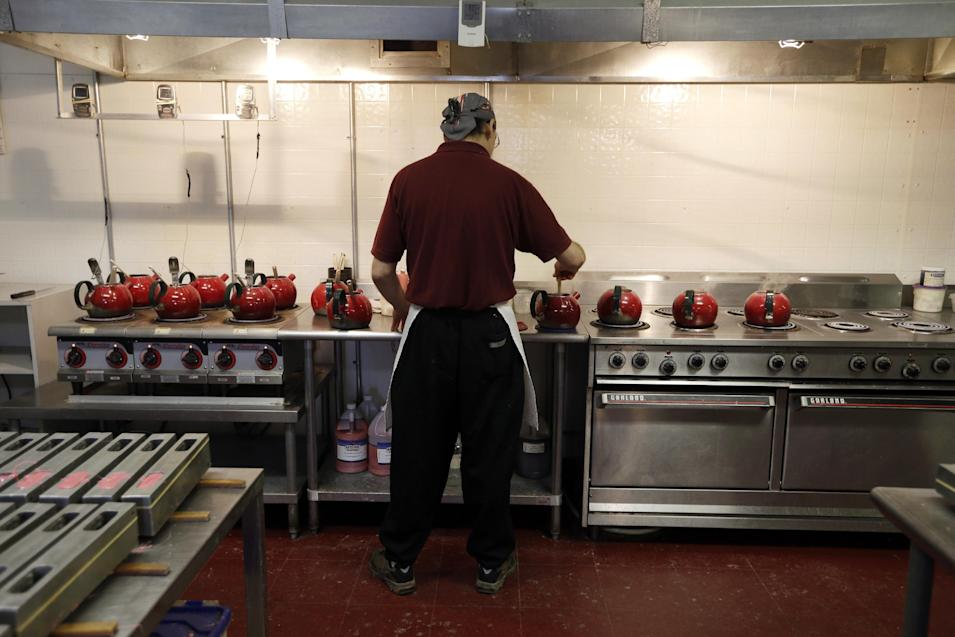 In this Dec. 6, 2012, photo, Blaine Serven heats peppermint mixture in teapots that will be used to make peppermint pigs at Saratoga Sweets in Halfmoon, N.Y. A holiday tradition in upstate New York has a peppermint twist: pig-shaped hard candies are sold with little metal hammers to be smashed at Christmas. (AP Photo/Mike Groll)
