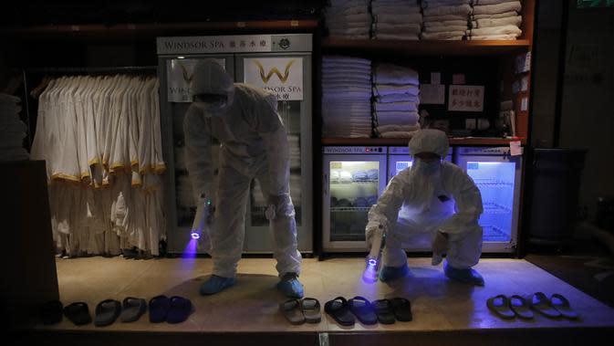 Staf mengenakan hazmat saat mendisinfesi fasilitas spa untuk mencegah penyebaran COVID-19 di Hong Kong, Kamis (17/9/2020). Pejabat pemerintah mengatakan akan semakin melonggarkan langkah-langkah jarak sosial, mengizinkan bar, taman hiburan dan kolam renang untuk kembali dibuka. (AP Photo/Kin Cheung)