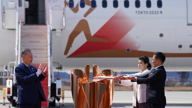 Presiden Olimpiade Tokyo 2020 Yoshiro Mori (kiri) menyaksikan dua atlet peraih tiga kali medali emas olimpiade Tadahiro Nomura (kanan) dan Saori Yoshida menyalakan obor Olimpiade saat tiba dari Yunani di Pangkalan Udara Matsushima, Prefektur Miyagi, Jepang, Jumat (20/3/2020). (AP/Eugene Hoshiko)
