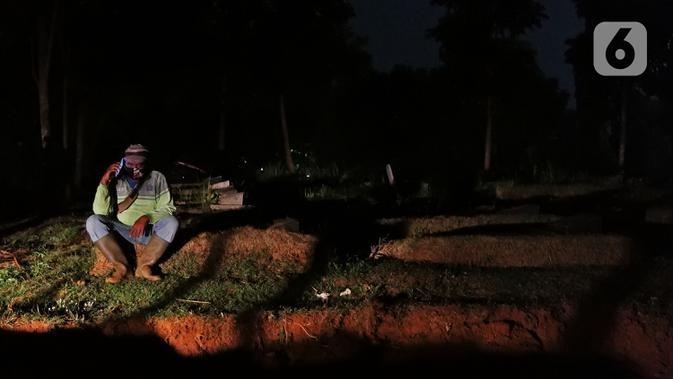 Petugas pemakaman menelepon keluarganya usai memakamkan jenazah pasien COVID-19 di TPU Pondok Ranggon, Jakarta, Selasa (14/7/2020). Hingga hari ini, lima provinsi mencatat tambahan kasus baru tertinggi yakni Jatim, DKI Jakarta, Sulsel, Kalsel, dan Sumut. (Liputan6.com/Herman Zakharia)