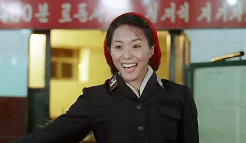 """In this image made out of film """"Comrade Kim Goes Flying"""" released by Another Dimension of An Idea/Koryo Group, Comrade Kim Yong Mi played by Han Jong Sim acknowledges applause from her comrades for her acrobatic performance. It's a classic tale of a small town girl who follows her dreams to the big city. But in this case, the girl is a North Korean coal miner, the big city is Pyongyang and her dream is to become a high-flying trapeze artist. """"Comrade Kim Goes Flying,"""" a collaboration between a North Korean director and two European filmmakers, makes its world premiere Saturday, Sept. 8, 2012 at the Toronto International Film Festival before it heads to Pyongyang later this month for its North Korean debut. (AP Photo/Courtesy of Another Dimension of An Idea/Koryo Group) EDITORIAL USE ONLY"""