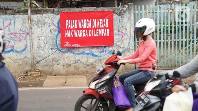 Pengendara motor melintas di depan poster protes warga terhadap pembangunan flyover di kawasan Tanjung Barat, Jakarta, Rabu (15/7/2020). Dalam poster protes tersebut, warga menuntut agar pembayaran pelunasan pembebasan lahan segera diselesaikan secara serentak. (Liputan6.com/Immanuel Antonius)