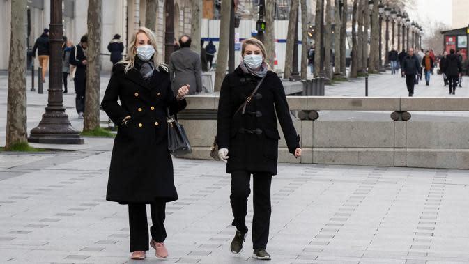 Wisatawan mengenakan masker saat berjalan di Jalan Champs Elysees, Paris, Prancis, 6 Maret 2020. Hingga Kamis (12/3/2020) pagi, jumlah kasus virus corona COVID-19 di Prancis sebanyak 2.284 orang terinfeksi, 48 meninggal, dan 12 sembuh. (AP Photo/Michel Euler)