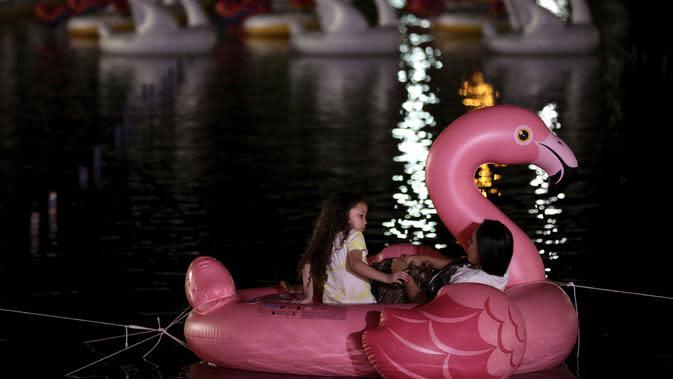 Seorang wanita dan anak bersantai di atas balon Flamingo di Danau Sarah Kubstichek saat mereka menonton film selama Festival Terapung di Brasilia, Brasil (30/9/2020). Konsep apung menjadi tren baru saat pandemi di beberapa negara seperti Israel dan Meksiko. (AP Photo/Eraldo Peres)