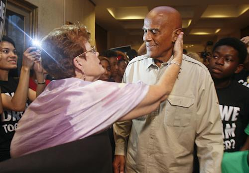 Barbara DeVane reaches out to kiss American singer, songwriter, actor and social activist Harry Belafonte, Jr. as he heads to Florida Gov. Rick Scott's office Friday, July 26, 2013 in the Capitol in Tallahassee, Fla. Dream Defenders were joined by Belafonte, Jr. as they went into their 11th day of a sit-in of Florida Gov. Rick Scott's office. The sit-in is their response to the 'not guilty' verdict in the trial of George Zimmerman, the Florida neighborhood watch volunteer who fatally shot Trayvon Martin. They are continuing to demand Scott call a special session. (AP Photo/Phil Sears)