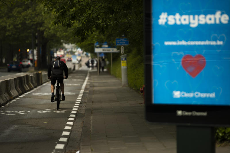 A man rides a bicycle along a new path designated only for bikes, during a gradual lifting of a lockdown to prevent the spread of the coronavirus, COVID-19, in Brussels, Monday, May 4, 2020. As European cities gradually relax lockdown measures, Brussels authorities intend to take advantage of the coronavirus health crisis to turn the EU institutions capital into a cycling-friendly greener place. (AP Photo/Francisco Seco)