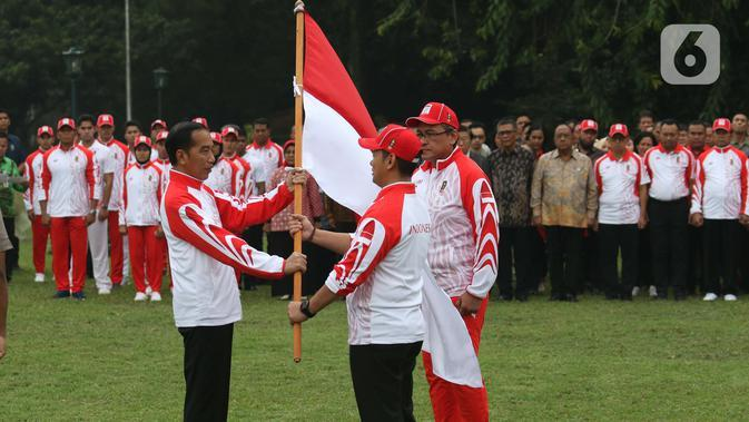 Presiden Joko Widodo atau Jokowi menyerahkan Bendera Merah Putih kepada Ketua National Olympic Committe (NOC) Raja Sapta Oktohari saat acara pelepasan Kontingen Indonesia untuk SEA Games 2019 Filipina di Istana Bogor, Rabu (27/11/2019). (Liputan6.com/Angga Yuniar)