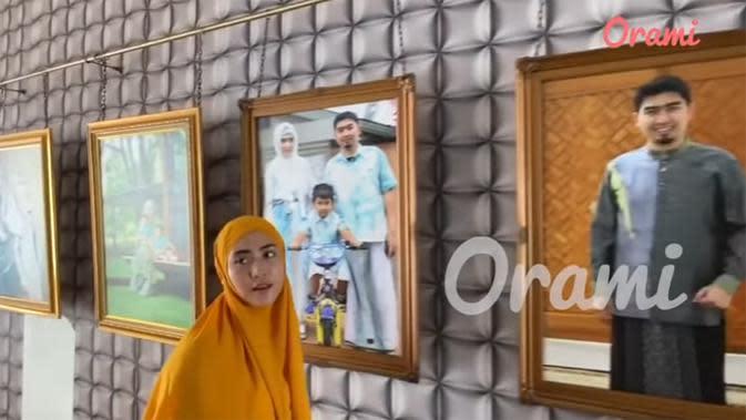 Tidak seperti biasa, foto yang ditempel, sedangkan April memperlihatkan koleksi foto yang telah di pigura di gantung. Ia mengaku, terinspirasi dengan model pajangan tersebut lantaran inspirasi maminya saat ke Dubai. (Youtube/Orami Indonesia)