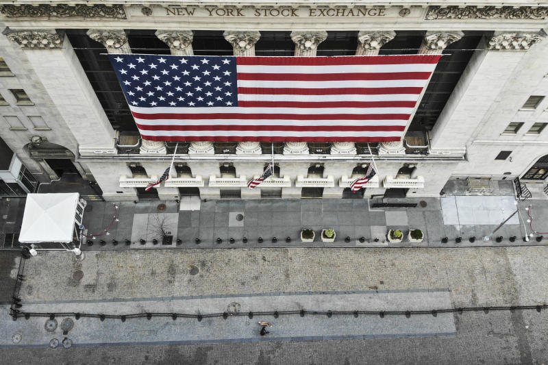 In this March 21, 2020 photo, a lone pedestrian walks his dog past the New York Stock Exchange as COVID-19 concerns empty a typically bustling downtown area in New York. New York Gov. Andrew Cuomo announced sweeping orders Friday that will severely restrict gatherings of any size for the state's more than 19 million residents and will require workers in nonessential businesses to stay home. (AP Photo/John Minchillo)