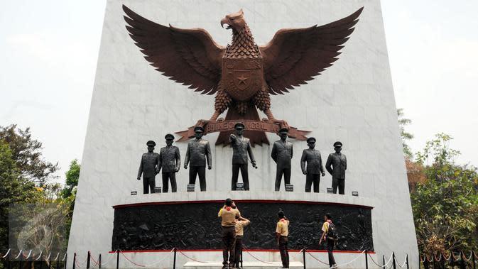 Sejumlah Pramuka mengabadikan patung tujuh pahlawan revolusi di Monumen Pancasila Sakti, Jakarta, Selasa (29/9/2015). Pemerintah akan mengadakan upacara peringatan Hari Kesaktian Pancasila pada 1 Oktober mendatang. (Liputan6.com/Helmi Fithriansyah)