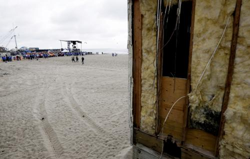 The insulation of a restroom on the Seaside Heights boardwalk is visible as people gather near a stage during a performance by musical group Fun, Friday, May 24, 2013, in Seaside Heights, N.J. New Jersey Gov. Chris Christie cut a ribbon to symbolically reopen the state's shore for the summer season, seven months after being devastated by Superstorm Sandy. Several beach communities have annual beach ribbon cuttings, announcing they are back in business. But this year's ceremonies are more poignant seven months after a storm that did an estimated $37 billion of damage in the state. (AP Photo/Julio Cortez)