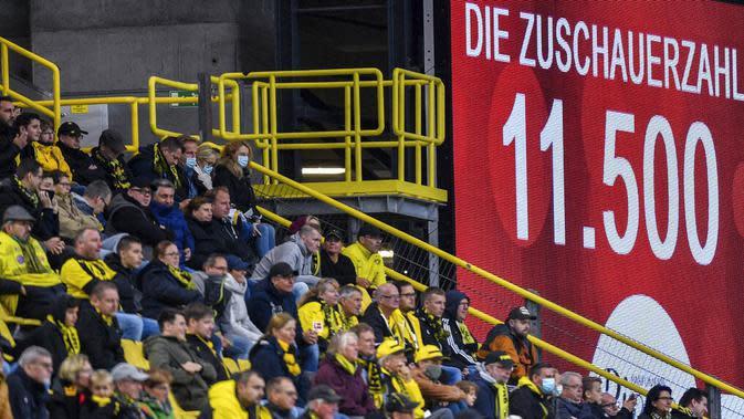 Suporter saat menyaksikan pertandingan antara SC Freiburg melawan Borussia Dortmund pada laga Bundesliga, Sabtu (3/10/2020). Sejumlah liga di Eropa telah mengijinkan fans menonton langsung pertandingan di stadion. (AP Photo/Martin Meissner)