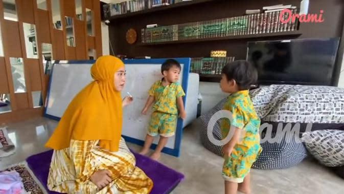 Masih di mushala, April terlihat mengajari dua anak kembarnya mengaji. Bintang sinetron itu mengaku tidak memaksakan anaknya saat sedang ngaji. (Youtube/Orami Indonesia)