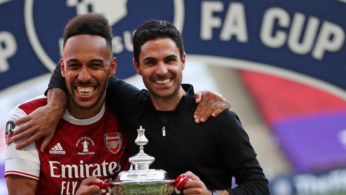 Pierre-Emerick Aubameyang bersama Mikel Arteta setelah Arsenal menjuarai Piala FA 2019/2020 di Stadion Wembley, London, Sabtu (1/8/2020). (Catherine Ivill/AFP)