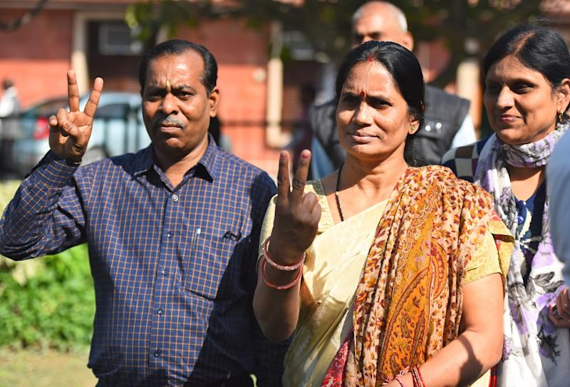 Asha Devi, mother of the 2012 Delhi gang rape victim, and her father Badrinath Singh show victory sign after a hearing at Supreme Court on March 16, 2020 in New Delhi. (Photo by Raj K Raj/Hindustan Times)