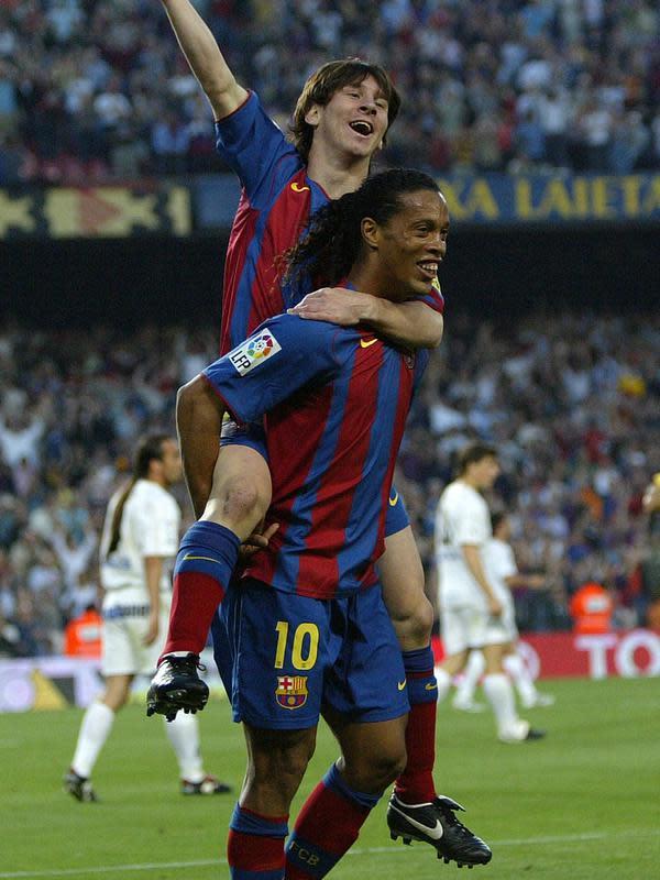Ronaldinho menggendong Lionel Messi usai memberikan assist untuk gol pertamanya bagi Barcelona. (AFP/Lluis Gene)