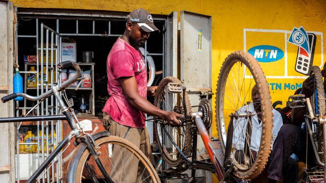 Seorang pria memperbaiki sepeda di Kampala, ibu kota Uganda (30/6/2020). Warga Uganda kini beralih menggunakan sepeda sebagai sarana transportasi yang mendukung di tengah pandemi COVID-19. (Xinhua/Hajarah Nalwadda)