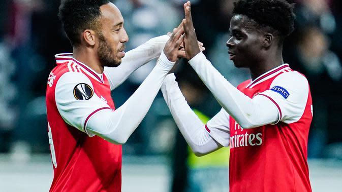 Penyerang Arsenal, Bukayo Saka (kanan) mendapat ucapan selamat dari Pierre-Emerick Aubameyang, setelah mencetak gol ke gawang Eintracht Frankfurt, di Frankfurt am Main, Jumat (20/9/2019) dini hari WIB. (AFP / Uwe Anspach)