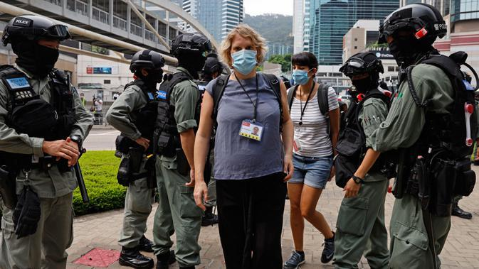 Polisi anti huru hara memeriksa kartu pers wartawan di luar gedung Dewan Legislatif di Hong Kong, Rabu (27/5/2020). Penjagaan ekstra dilakukan menimbang kemungkinan aksi menentang Rancangan Undang-undang (RUU) yang mengkriminalkan penghinaan terhadap lagu kebangsaan China. (AP Photo/Kin Cheung)