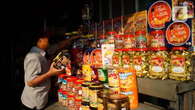 Seorang pria melihat dagangan kue kering di salah satu toko penjualan kue kering di kawasan Ciracas, Jakarta, Selasa (19/5/2020). Adanya pandemi covid-19 diakui para pedagang menyebabkan penjualan kue kering menjelang lebaran turun hingga 50 persen. (Liputan6.com/Immanuel Antonius)