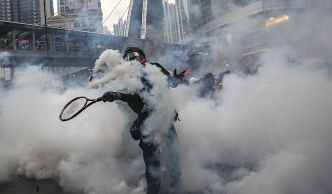 A protester uses a tennis racket to return a tear-gas canister in Hong Kong. Photo: Sam Tsang