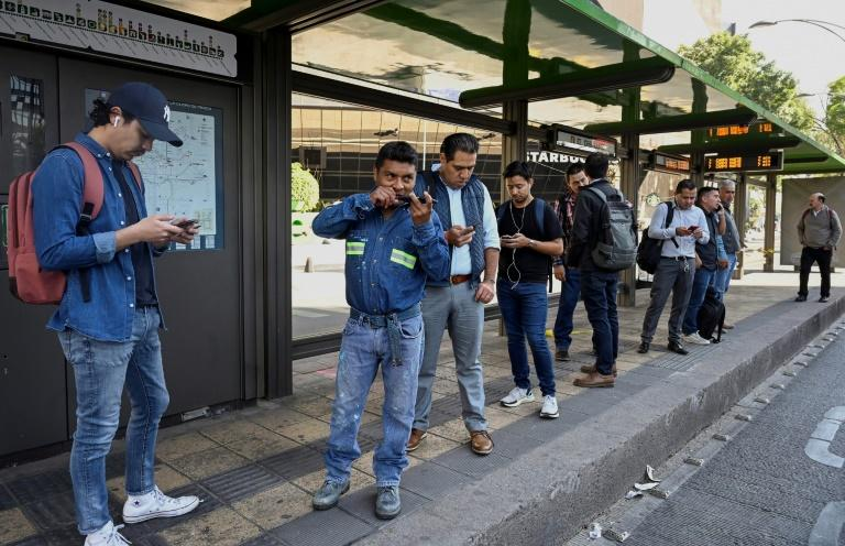 Men wait for the bus at the Hidalgo metrobus station during the Women National Strike called 'A Day Without Us' in Mexico City, on March 9, 2020