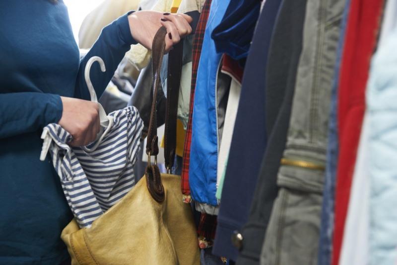woman shoplifting putting clothing into purse