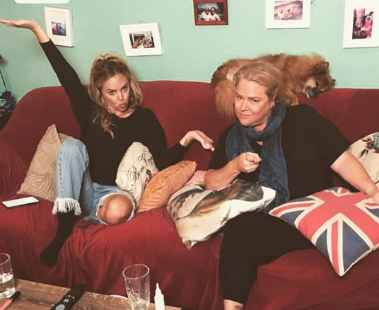 Angie Kent and Yvie Jones pose on their couch, where they starred on Gogglebox