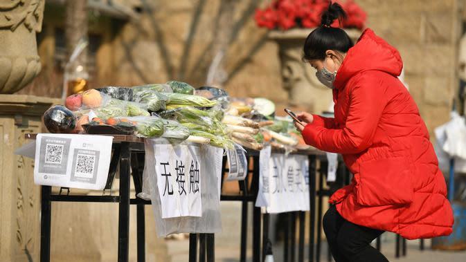Seorang wanita membeli sayuran dan membayar dengan kode QR di kios sayur tak berpenjaga di sebuah permukiman di Distrik Xinhua, Shijiazhuang, ibu kota Provinsi Hebei, China utara (12/2/2020). (Xinhua/Xu Jianyuan)