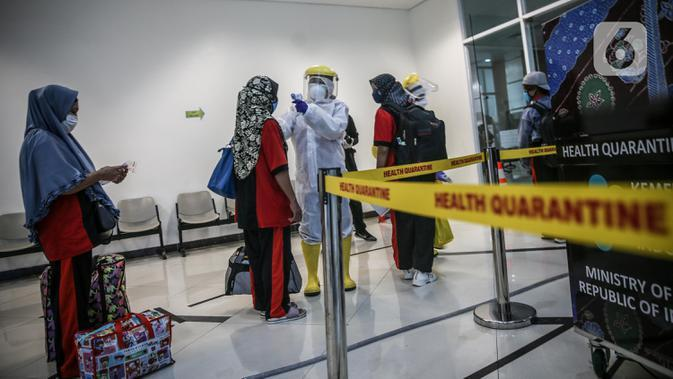 Sejumlah TKI Ilegal yang dipulangkan dari Malaysia diukur suhu tubuhnya setibanya di Pelabuhan Tanjung Priok, Jakarta, Jumat (12/6/2020). Sebanyak 436 TKI Ilegal tersebut nantinya akan dipulangkan ke daerah asalnya di 22 provinsi. (Liputan6.com/Faizal Fanani)