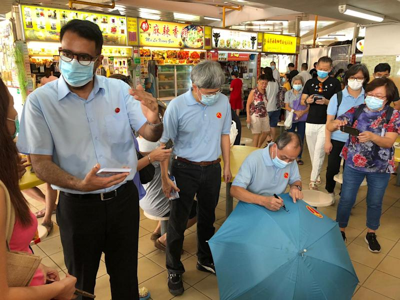 Workers' Party's secretary-general Pritam Singh (left) chats with residents during a party walkabout at the Kovan Market and Food Centre. Former party chief Low Thia Khiang (seated) was also present. (PHOTO: Nicholas Yong/Yahoo News Singapore)