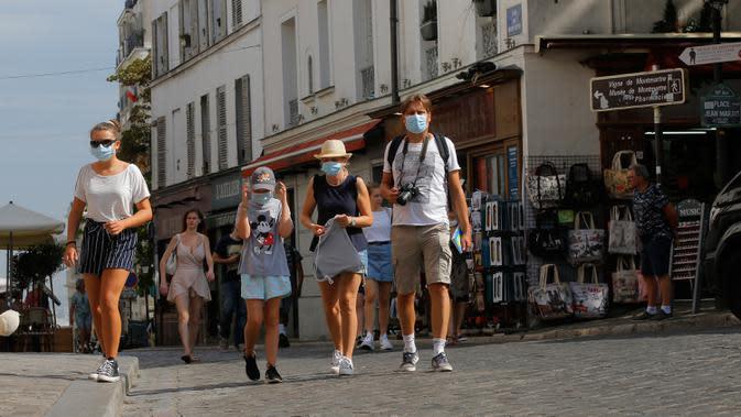 Turis mengunjungi distrik Montmartre di Paris pada Senin (10/8/2020). Pemerintah Kota Paris mengumumkan masker wajib dipakai di area luar ruangan yang ramai di ibu kota Prancis itu mulai Senin (10/8) untuk mengendalikan peningkatan tingkat infeksi virus corona. (AP Photo/Michel Euler)