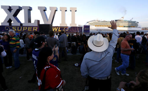 Rodolfo Rodriguez, center right, of Monterrey, Mexico, waves at a cruise ship arriving into the Port of New Orleans near the Roman numerals for Super Bowl XLVII at Woldenberg Riverfront Park, Saturday, Feb. 2, 2013, in New Orleans. The city will host NFL football's Super Bowl XLVII between the Baltimore Ravens and the San Francisco 49ers on Sunday. (AP Photo/Julio Cortez)