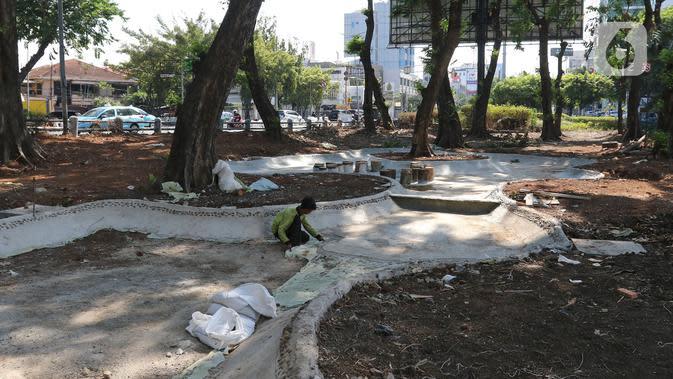 Petugas Dinas Kehutanan Jakarta Barat menyelesaikan pembangunan kolam di kawasan Tomang, Jakarta, Selasa (19/11/2019). Pembangunan taman tersebut dilengkapi dengan rumah pohon untuk menambah ruang bermain anak. (Liputan6.com/Herman Zakharia)