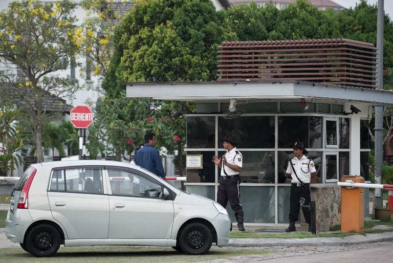 Security men guard the entrance to the residential complex where captain Zaharie Ahmad Shah, pilot of the missing Malaysia Airlines flight MH370, lives in Shah Alam, west of Kuala Lumpur, on March 15, 2014
