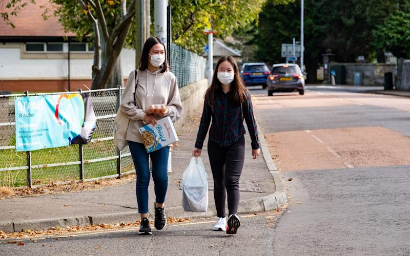Two students make their way back to University halls of residence after going out to pick up essential food items on Saturday - Stuart Nicol/Stuart Nicol Photography
