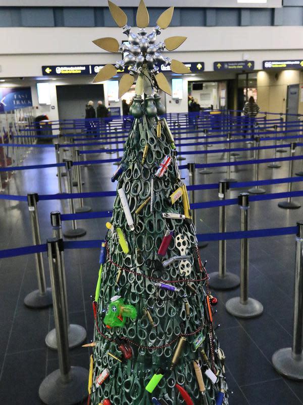 Pohon Natal yang dirakit dari barang-barang sitaan di Bandara Vilnius, Lithuania pada 12 Desember 2019. Bagian tubuh pohon Natal dibuat dengan menggunakan gunting yang dicat warna hijau agar terlihat seperti daun. . (Photo by Petras Malukas / AFP)