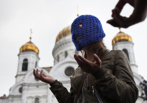 An unidentified supporter of Pussy Riot speaks to the assembled press outside the Christ the Saviour Cathedral, in Moscow, Wednesday, Aug. 15, 2012. The global campaign to free Pussy Riot is gaining speed. Supporters of the punk provocateur band mobilize this week in at least a two dozen cities worldwide to hold simultaneous demonstrations an hour before a Russian court rules on whether its members will be sent to prison. (AP Photo/Alexander Zemlianichenko)