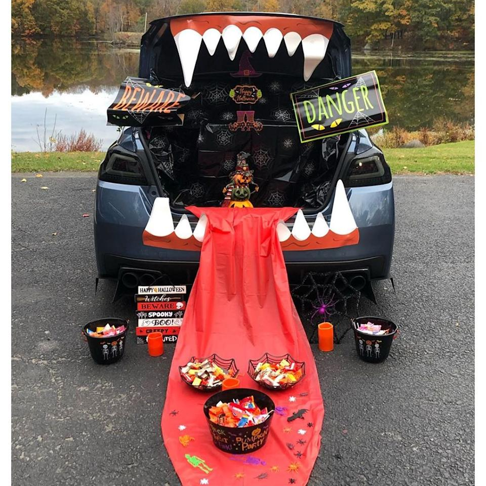 """<p>Take a big, toothy bite out of the spooky holiday with this vampire fangs-inspired trunk-or-treat theme. You can purchase the big chompers online and craft your own tongue out of a disposable tablecloth. Throw in some festive signs for some extra flair, and you are set!</p><p><a class=""""body-btn-link"""" href=""""https://go.redirectingat.com?id=74968X1596630&url=https%3A%2F%2Fwww.bedbathandbeyond.com%2Fstore%2Fproduct%2Fnational-tree-company-reg-tricky-trunks-trade-bright-eyes-car-kit%2F5200083%3Fkeyword%3Dtrunk-or-treat&sref=https%3A%2F%2Fwww.bestproducts.com%2Fparenting%2Fg33658548%2Funique-trunk-or-treat-ideas%2F"""" target=""""_blank"""">Shop Trunk Teeth</a></p><p><strong>More: </strong><a href=""""https://www.bestproducts.com/parenting/g33575561/halloween-face-masks-for-kids/"""" target=""""_blank"""">Keep Up the Festivities This Season With These Halloween Masks for Kids</a></p>"""