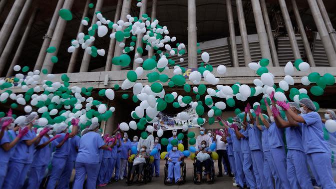 Petugas medis melepaskan balon saat merayakan tiga pasien terakhir yang meninggalkan rumah sakit lapangan di Stadion Nasional Mane Garrincha di Brasilia, Brasil, Kamis (15/10/2020). Para tenaga kesehatan berkumpul saat pasien COVID-19 terakhir pulang setelah dinyatakan sembuh (AP Photo/Eraldo Peres)
