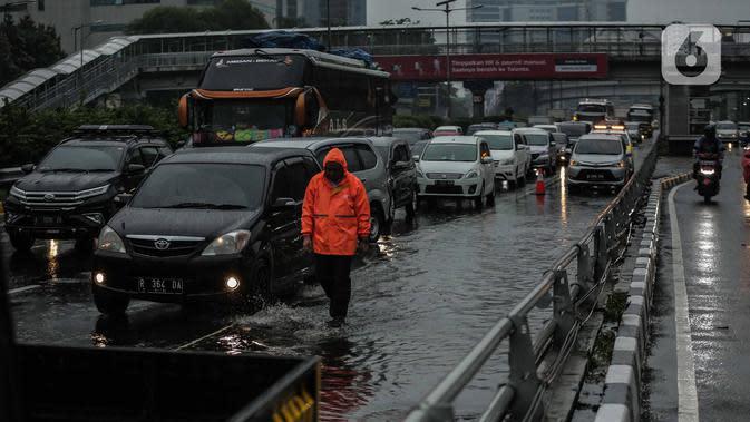 Petugas berjalan di antara kendaraan yang terjebak kemacetan di ruas Tol Dalam Kota (Dalkot), Jakarta, Selasa (17/12/2019). Air hujan sempat menggenangi sebagian ruas Tol Dalam Kota untuk arah Kuningan arah Cawang hingga sempat membuat lalu lintas tersendat. (Liputan6.com/Faizal Fanani)