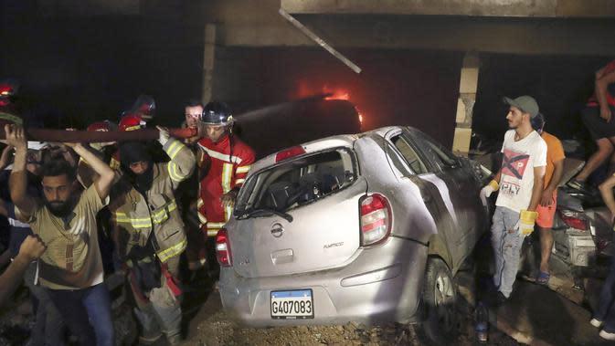 Petugas pemadam kebakaran memadamkan api di gedung setelah tangki bahan bakar meledak di lingkungan Tariq al-Jdide di Beirut (9/10/2020). Upaya penyelamatan korban masih berlangsung di lokasi. (AP Photo/Bilal Hussein)