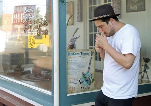 In this Sept. 5, 2013, photo Marcus Mumford, of the band Mumford & Sons, lights a cigarette as he walks out of Byron Berline's Double Stop Fiddle Shop in Guthrie,, Okla. The population of the small Oklahoma town is expected to quadruple this weekend as people come to watch the British folk rock band on the second stop of the Mumford & Sons' Gentlemen of the Road concert series in Guthrie. (AP Photo/Sue Ogrocki)