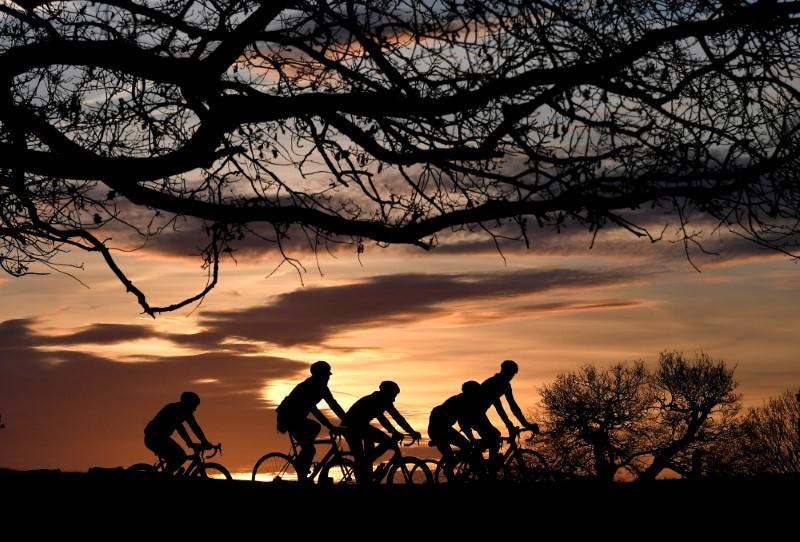 FILE PHOTO: Cyclists ride at sunrise in London