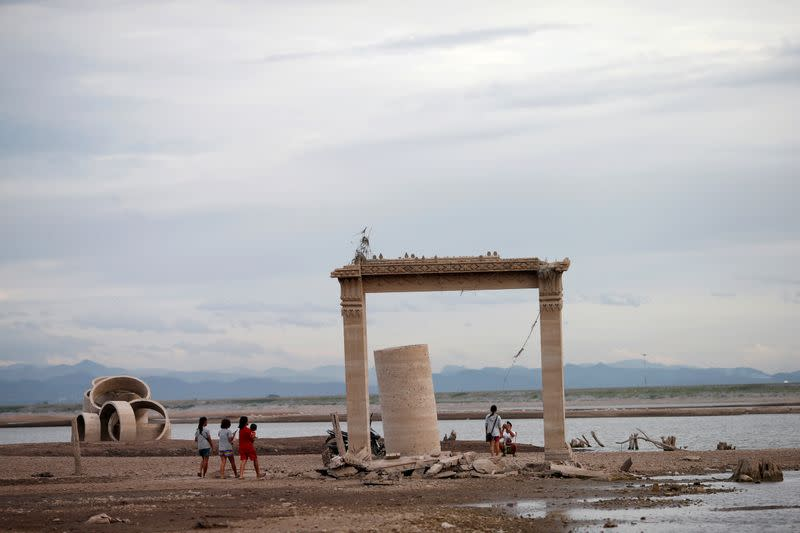 FILE PHOTO: People walk through the ruins of an old Buddhist temple, which has resurfaced in a dried-up dam due to drought, in Lopburi, Thailand